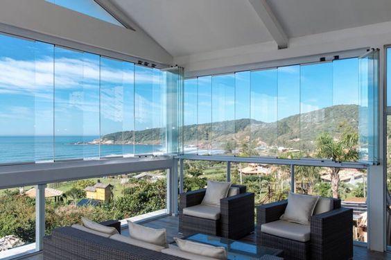 Cortina de varanda de vidro com móveis confortáveis