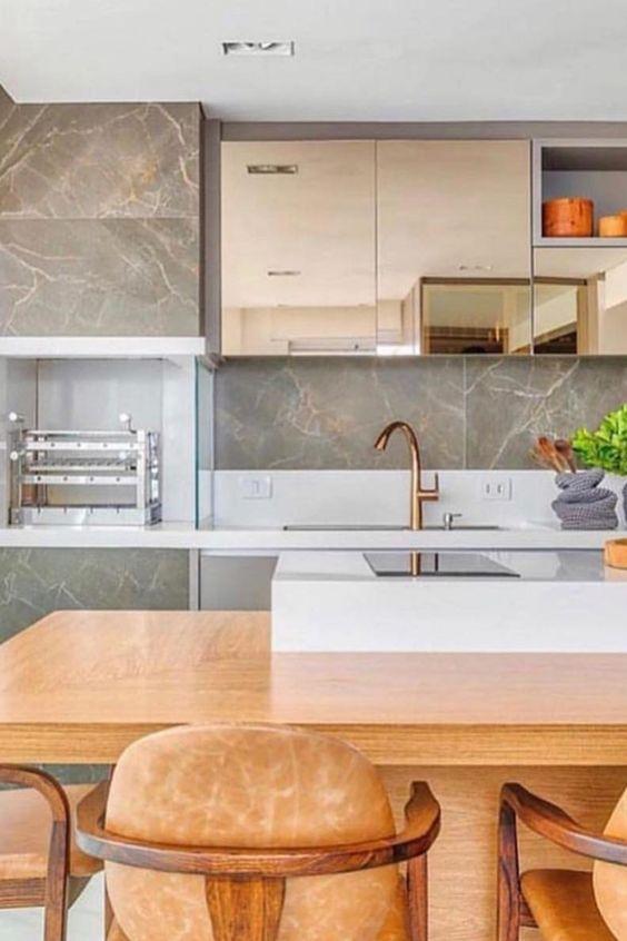 Cozinha planejada com churrasqueira de parede e revestimento marmorizado