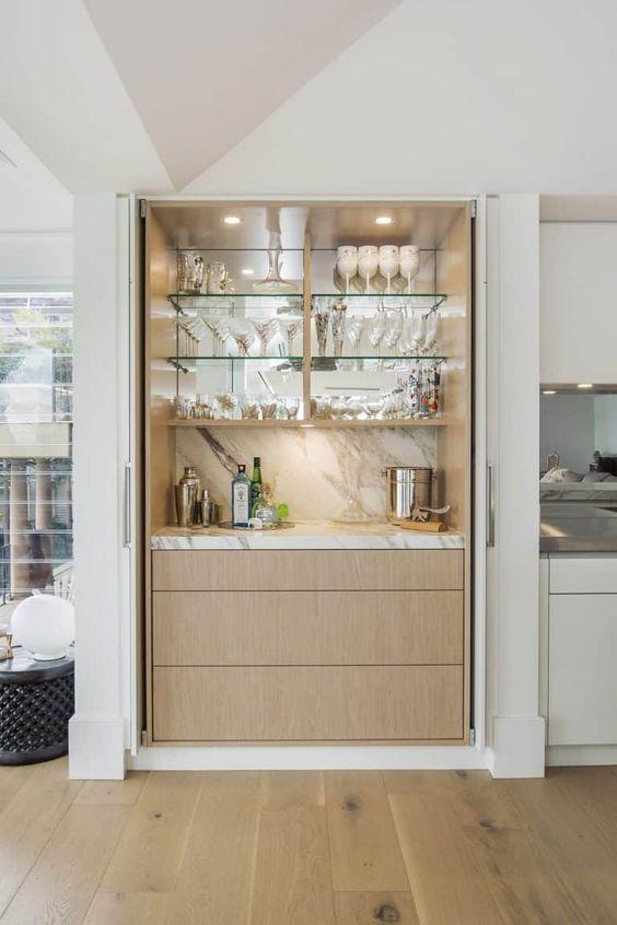 Decoração planejada com cristaleira de parede e bar em casa