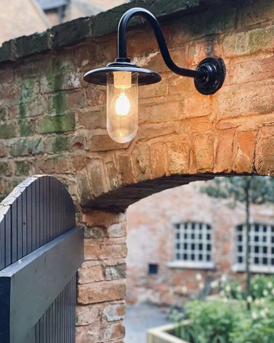 Entrada de casa com arandela industrial decorando o ambiente