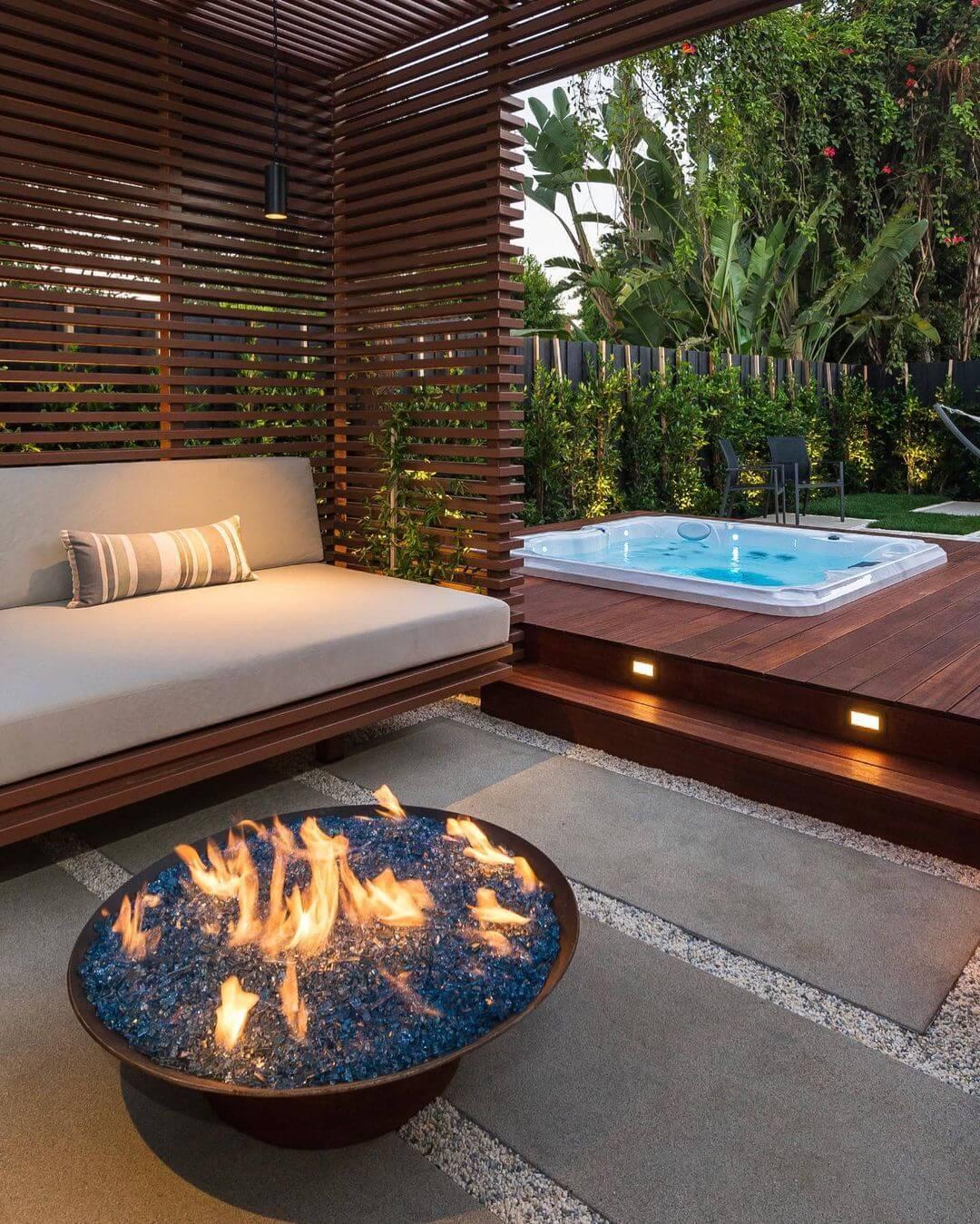 Jacuzzi externa com sofa de madiera e lareira