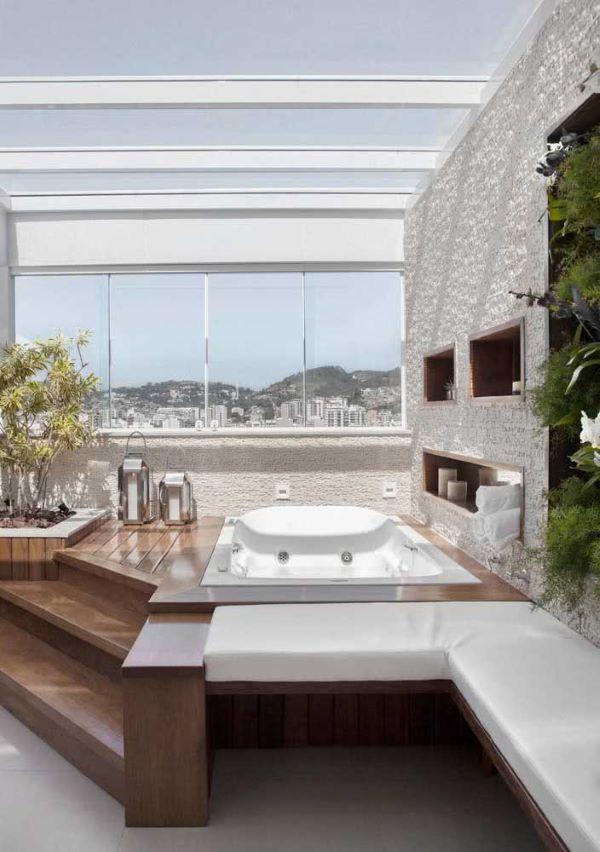 Jacuzzi externa na varanda de vidro iluminada
