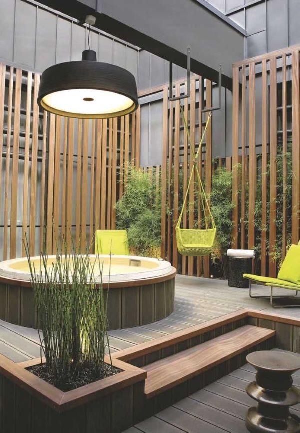 Jacuzzi externa redonda com deck de madeira e rede de descanso