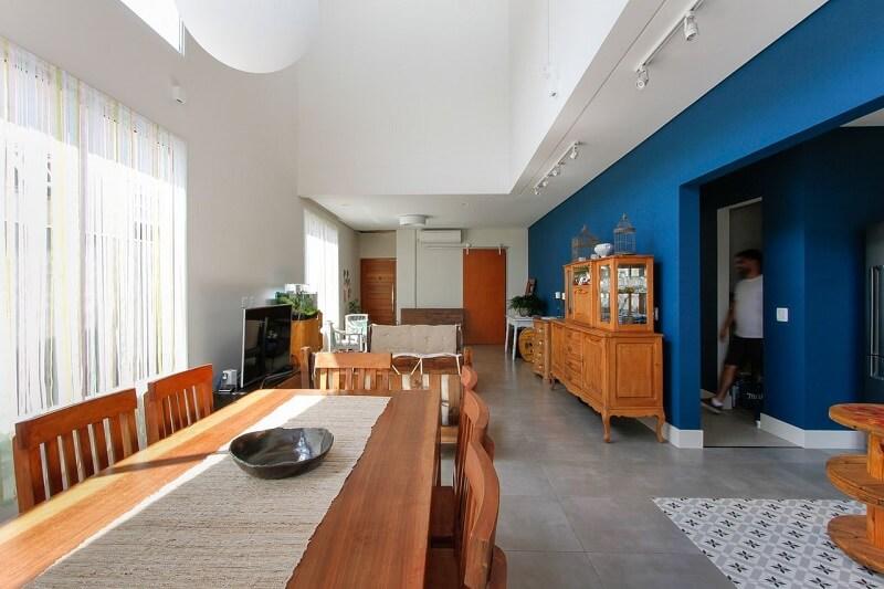 Móveis em madeira, piso fosco e paredes azuis marcam a decoração do espaço. Projeto por Otoni Arquitetura