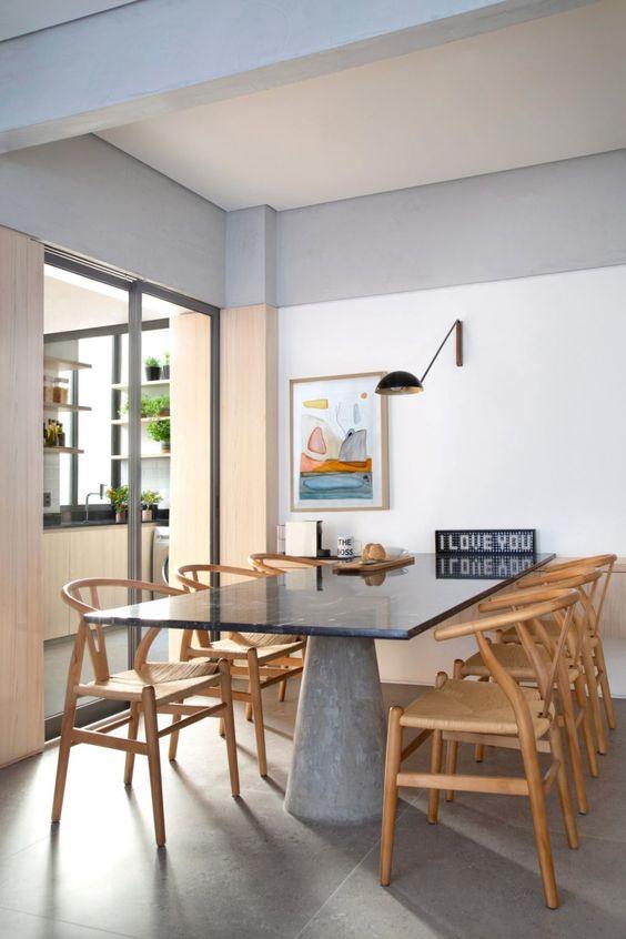 Mesa de granito cinza com cadeiras de madeira