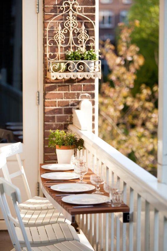 Mesa para sacada de madeira com pratos de porcelana