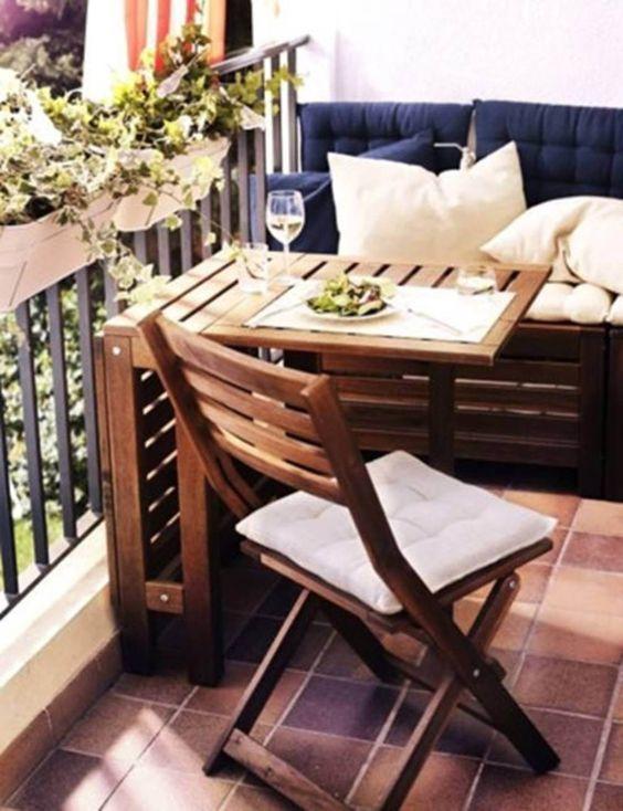 Mesa para sacada de madeira com sofá azul marinho