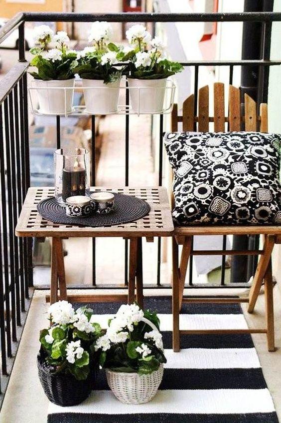 Mesa para sacada pequena decorada com flores brancas com almofada preta e branca