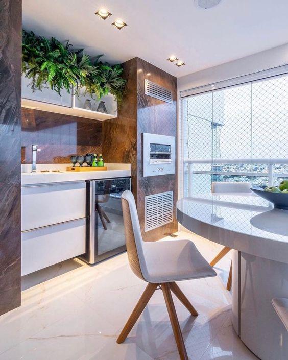 Mesa para sacada redonda e branca com churrasqueira e móveis planejados
