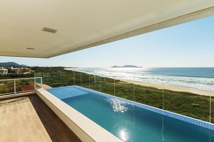 Modelo de piscina retangular com prainha instalada com vista para o mar. Projeto por Mantovani e Rita
