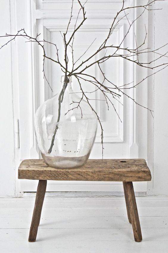 Sala com banco rustico e vaso de vidro
