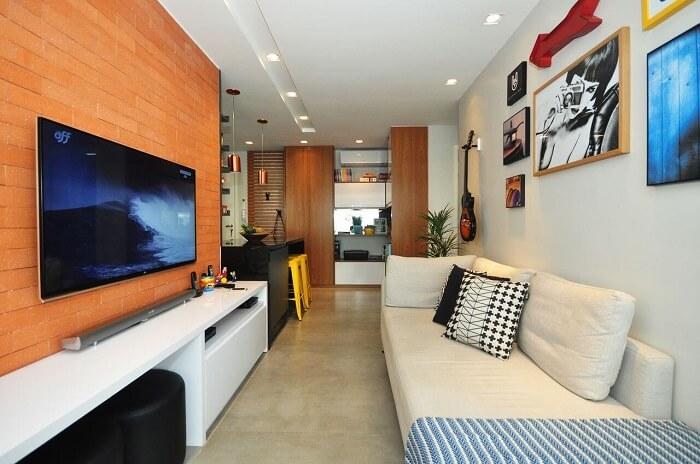 Sala de estar com piso fosco cinza e parede com tijolinhos aparentes. Projeto de Condecorar