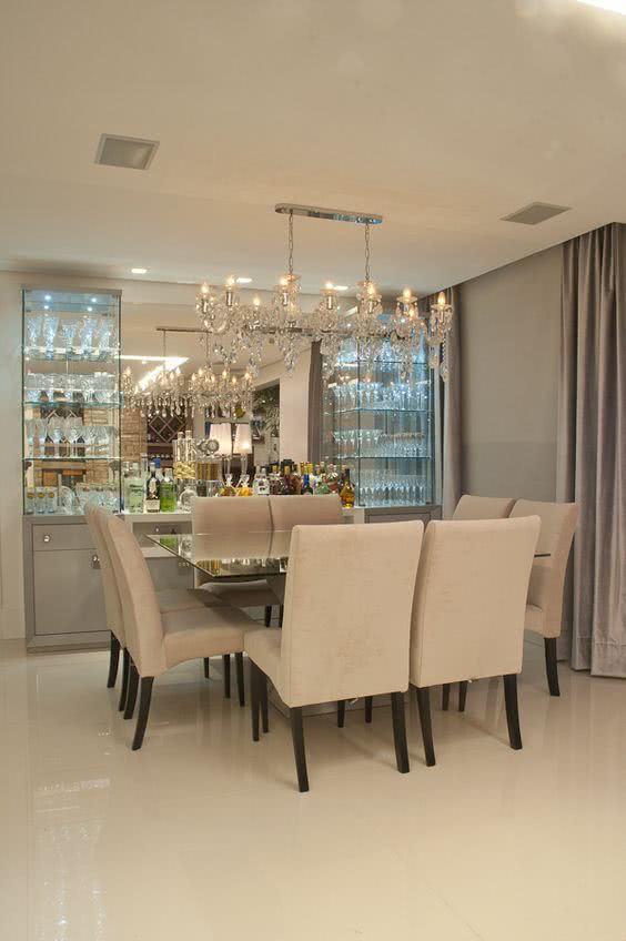 Sala de jantar com cristaleira de parede de vidro e luxuosa