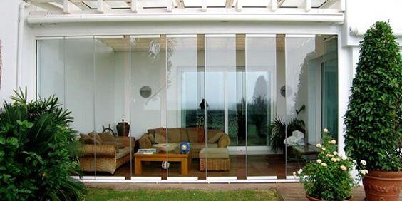 Varanda com cortina de vidro e móveis rústicos