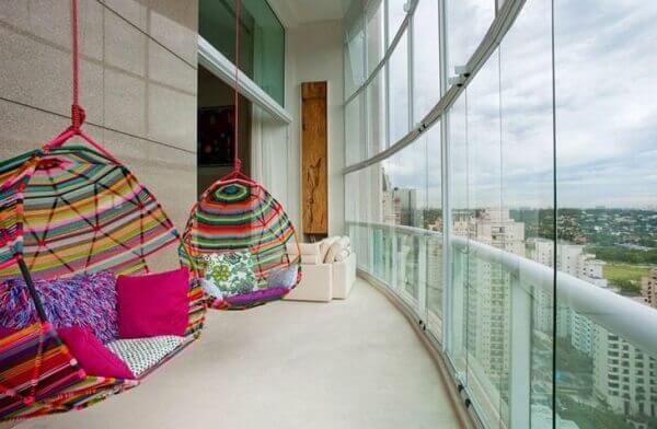 Varanda de vidro com cadeira de balanço colorida