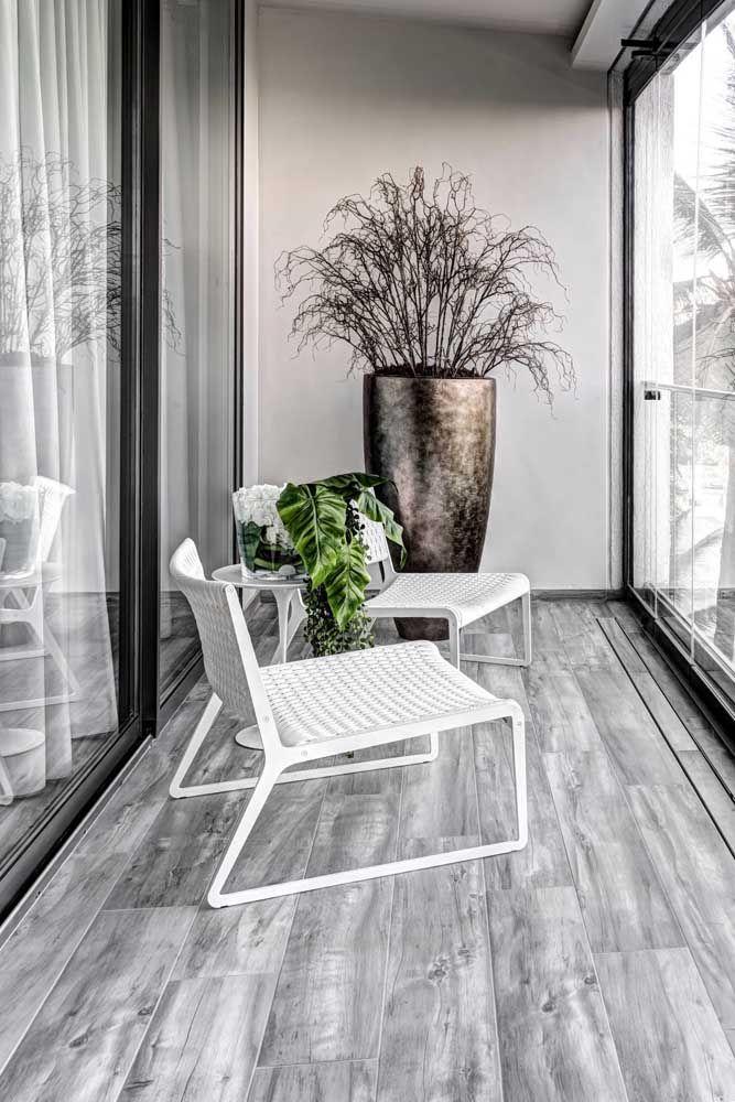 Varanda de vidro com cadeiras brancas