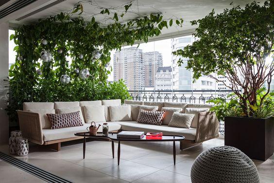 Varanda de vidro com decoração de plantas e sofás modernos