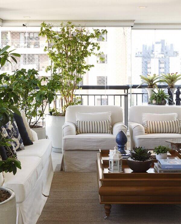 Varanda de vidro com móveis brancos