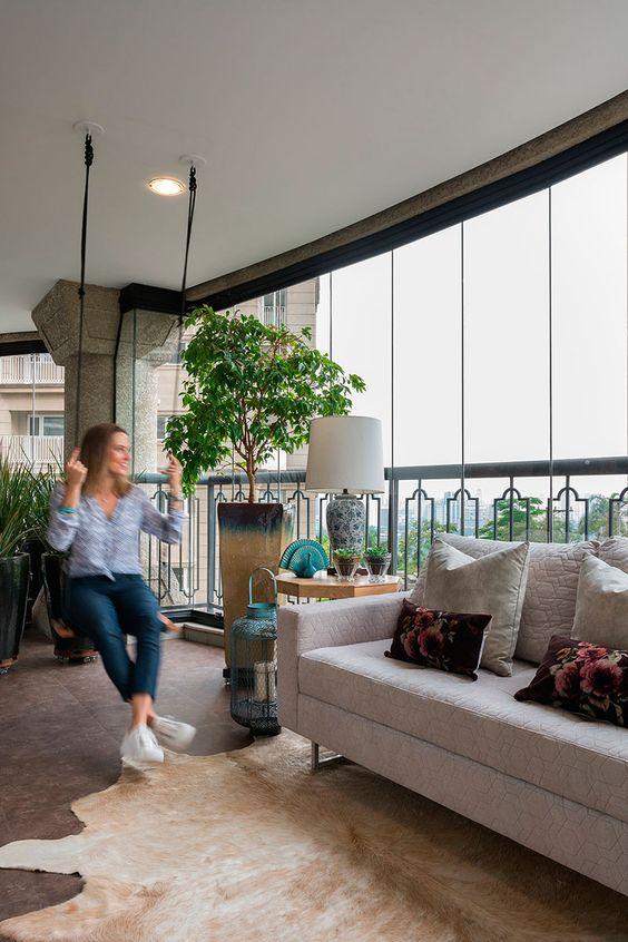 Varanda de vidro com móveis clássicos e balanço