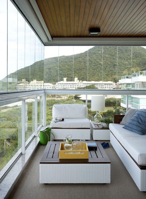 Varanda de vidro com móveis confortáveis branca