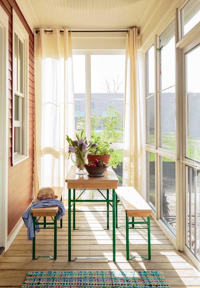Varanda de vidro com móveis de madeira rústicos com vista para o jardim
