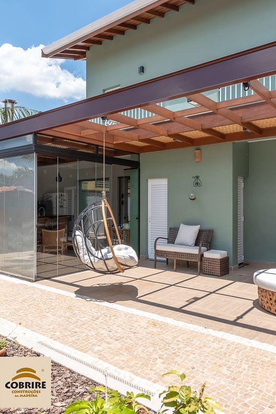 Varanda de vidro com pergolado de madeira