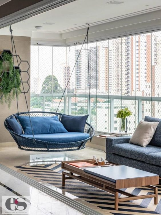 Varanda de vidro com sofá de balanço azul