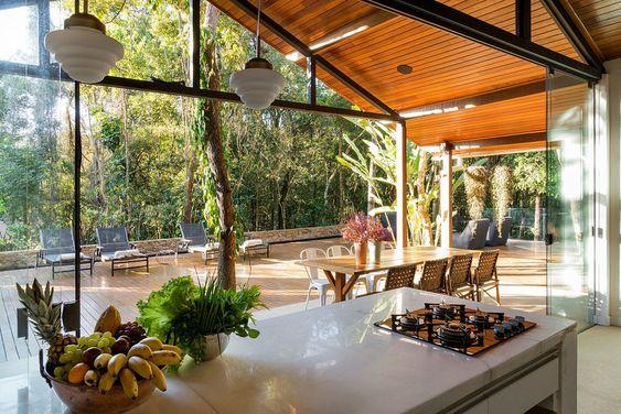 Varanda de vidro em casa ampla com jardim