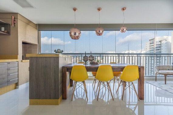 Varanda gourmet com cortina de vidro e móveis coloridos