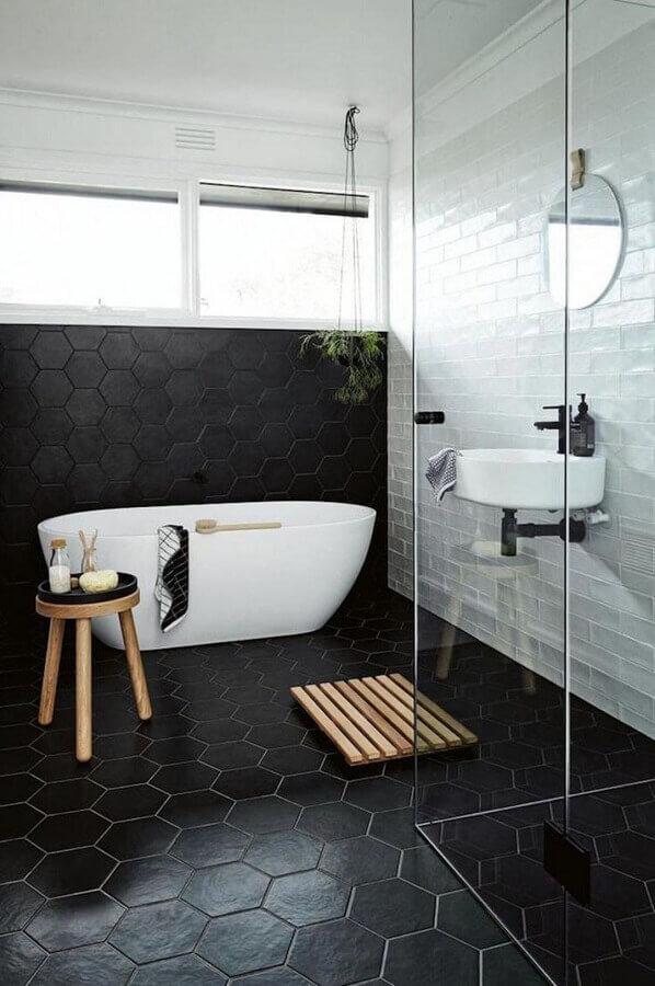 banheiro minimalista decorado com revestimento preto fosco hexagonal que se estende para o piso Foto Pinterest