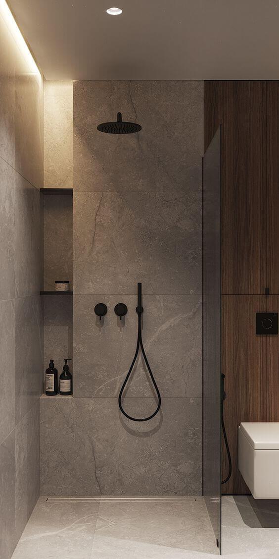 Banheiro com revestimento de cimento queimado e chuveiro preto