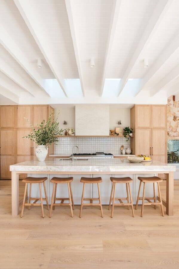banquetas para ilha de cozinha grande decorada com armários de madeira Foto House & Home