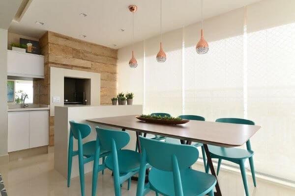 Área gourmet pequena com churrasqueira e mesa com cadeiras azuis turquesa