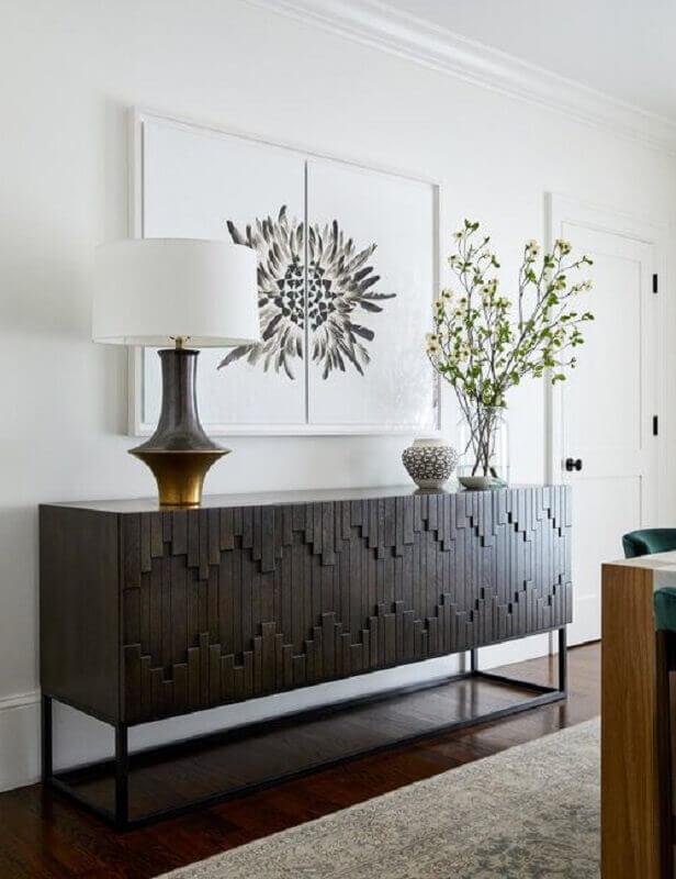decoração de sala branca com armário buffet de madeira com detalhes na porta Foto Braun + Adams