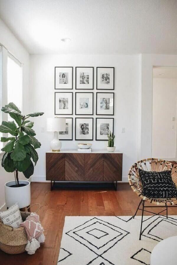 decoração de sala com quadros de parede e armário buffet de madeira  Foto Sarah Elizabeth Ray