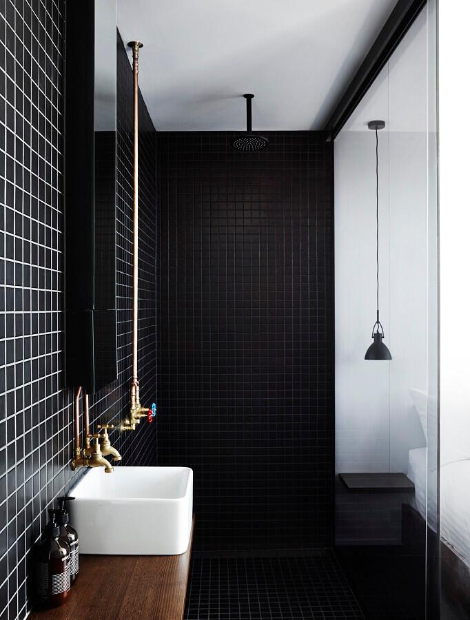 decoração minimalista de banheiro com revestimento preto e bancada de madeira Foto The Local Project
