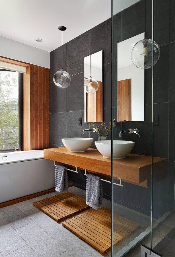 luminária decorativa de teto para banheiro decorado com parede preta e bancada de madeira Foto Hometeka