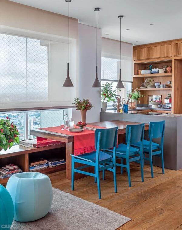 Mesa para sacada com cadeira azul e pendentes industriais