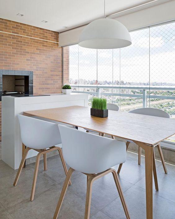 Mesa para sacada de madeira com cadeiras brancas e lustre branco combinando