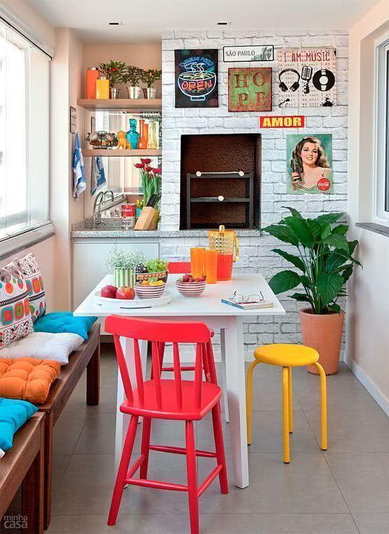 Mesa branca com cadeiras coloridas na decoração vintage da sacada