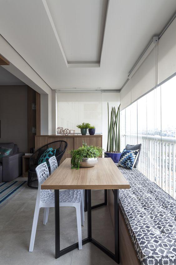 Sacada pequena com mesa de madeira e móveis planejados