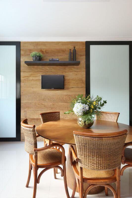 Mesa para varanda moderna com televisão e plantas na decoração