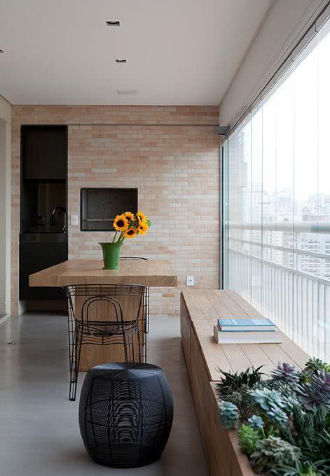 Mesa para sacada gourmet pequena com churrasqueira e cortina de vidro