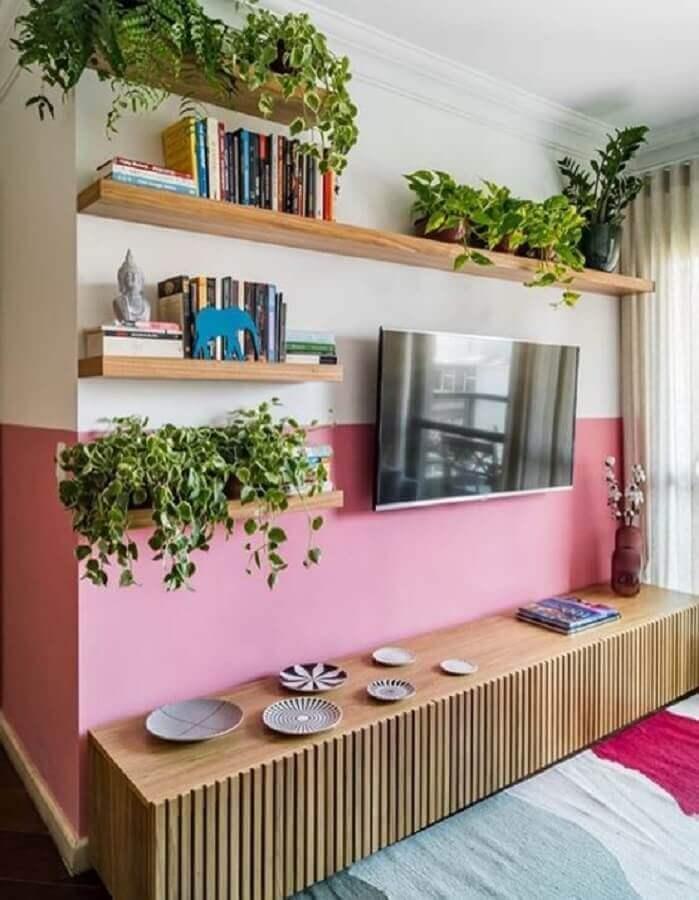 pintura meia parede rosa para sala de TV decorada com rack de madeira e vasos de plantas Foto Jeito de Casa