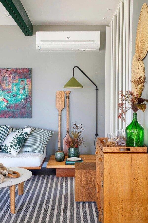 sala de estar moderna decorada com tapete listrado e luminária decorativa de parede Foto Casa de Valentina