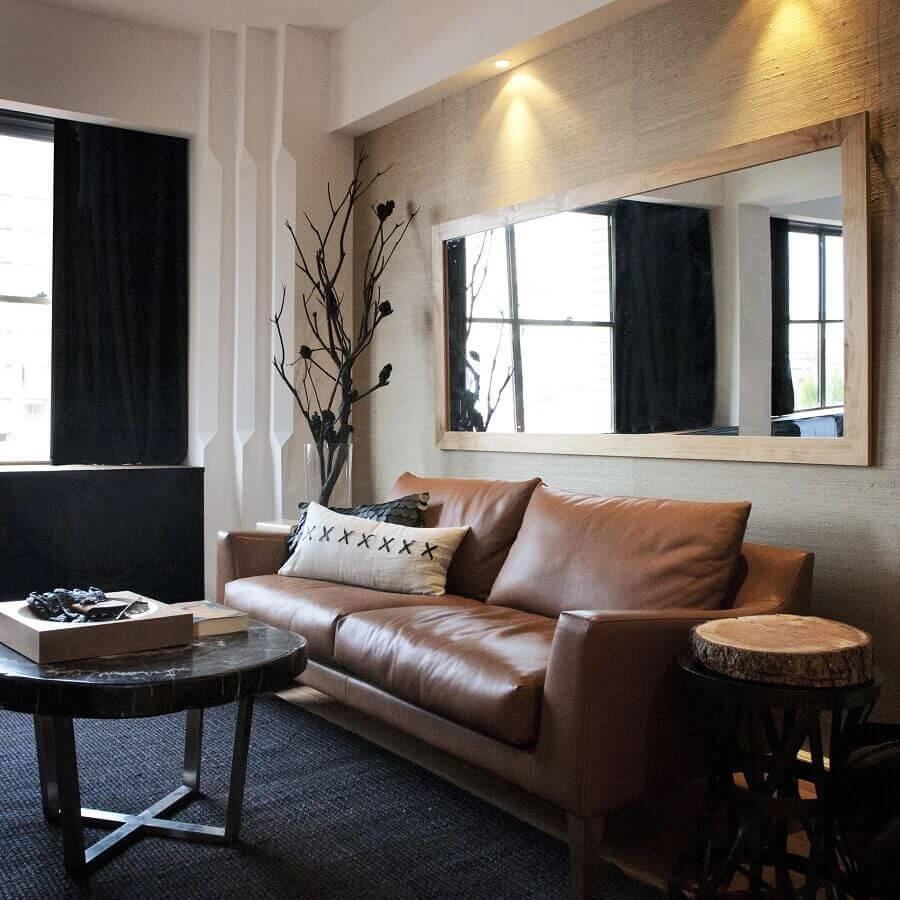 sala de visita decorada com sofá de couro e espelho com moldura de madeira Foto Pinterest