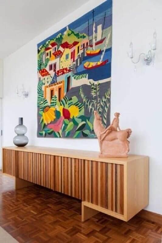 sala decorada com armário buffet de madeira grande e quadro colorido Foto Jeito de Casa