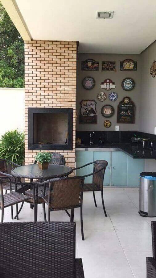 Área da churrasqueira gourmet com revestimento de tijolinho e armários azuis na decoração moderna