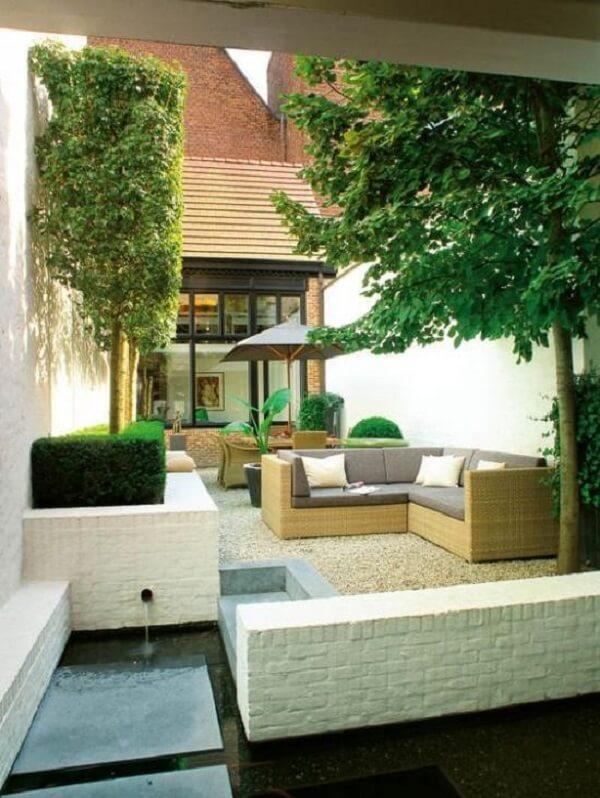 Área externa com móveis de vime e jardim com pedra branca. Fonte: Pinterest