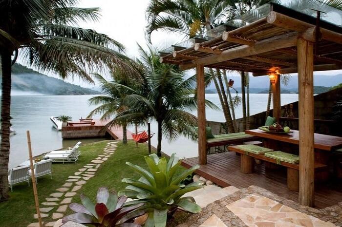 Área externa com pergolado de madeira e jardim com pedras que direcionam ao deck de madeira. Fonte: Urbano Studio
